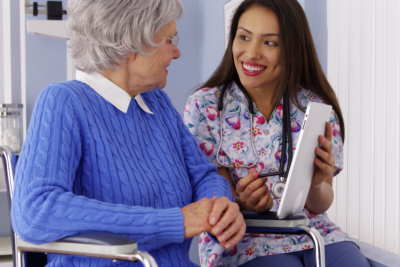 Mexican caregiver talking to elderly patient with tablet