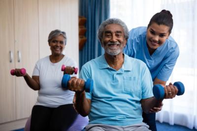 Nurse training seniors in lifting dumbbells