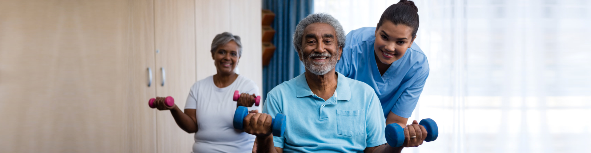 Nurse training seniors in lifting dumbbells